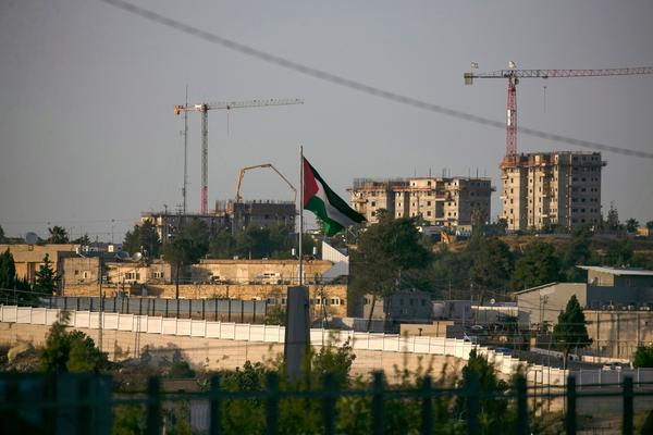A Palestinian flag waves at the northern entrance to the city of Ramallah in the occupied West Bank as construction works take place in the Israeli settlement of Beit El in the background. Israel intends to annex West Bank settlements and the Jordan Valley, as proposed by President Trump, with initial steps slated to begin July 1.
