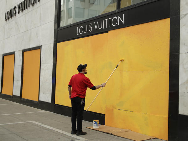 A worker paints over a Louis Vuitton storefront, boarded up after the coronavirus outbreak, on March 30 in San Francisco.