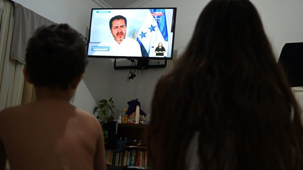Two children watch a national address by Honduran President Juan Orlando Hernández on Tuesday, during which he confirmed he tested positive for the coronavirus.