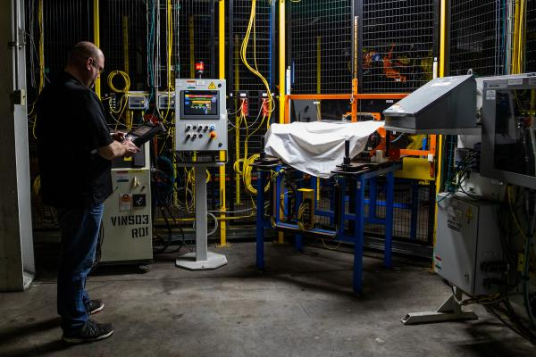 Dan Tasiemski, director of general assembly at the Lordstown Motors assembly plant in Ohio, works to revive a robot on the assembly floor of the factory.