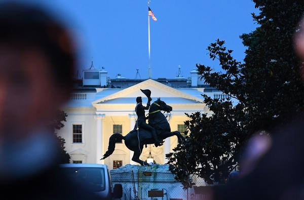 Police officers stand guard with the statue of former President Andrew Jackson after protesters tried to topple it Monday in Lafayette Square in Washington, D.C.