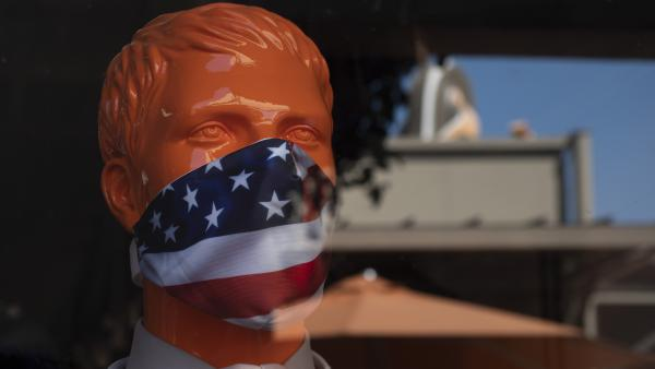 """A mannequin wears a face mask at the Citadel Outlets in Commerce, Calif. Gov. Gavin Newsom on Thursday urged Californians to turn to their """"better angels"""" and use common sense over the holiday weekend by wearing a mask and skipping traditional gatherings with family and friends."""