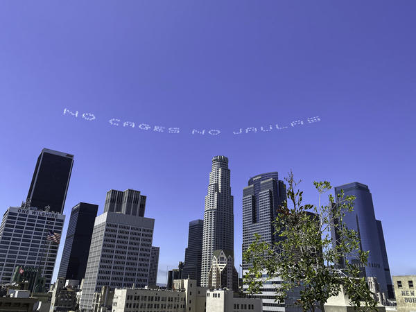 """The words """"No Cages No Jaulas"""" appear over downtown Los Angeles as part of a day of activism by artists nationwide to mark the July 4 holiday. The message was designed by the artist Beatriz Cortez."""