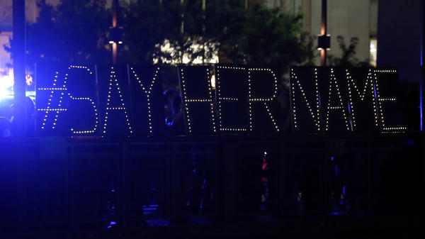 "Protesters hold up a lighted sign reading ""#sayhername"" during a July 2015 vigil for Sandra Bland in Chicago. Bland died in a Texas jail after a traffic stop escalated into a physical confrontation. Authorities said Bland hanged herself, a finding her family disputed."