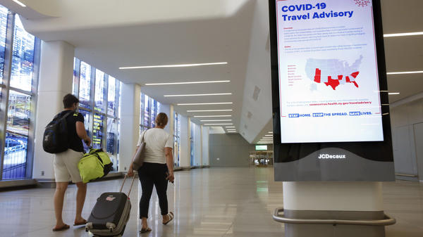 Arriving travelers walk by a COVID-19 travel advisory sign in the baggage claim area at New York City's LaGuardia Airport. New York state is requiring travelers from states on its quarantine list to show proof that they've completed a form with their contact information.