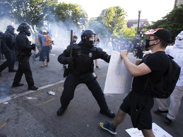 A law enforcement officer raises a baton and tear gas is fired during protests near the White House on June 1.