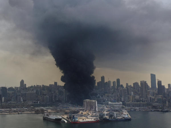 A column of black smoke rises from a fire Thursday at a warehouse at Beirut's port. A Lebanese official said the fire is under control, according to local media.
