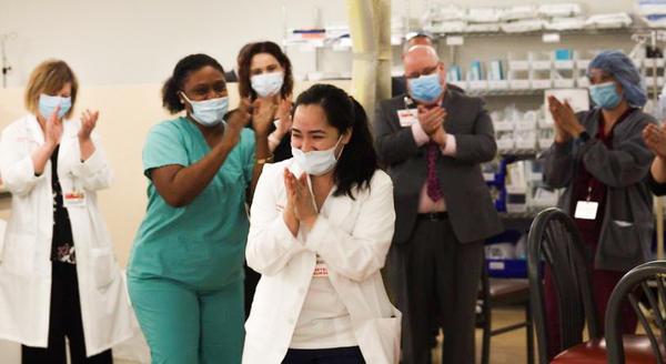 "Nurses clap after Kym Villamer and her colleague Dawn Jones sing ""Ain't No Mountain High Enough"" at <a data-cid=""12680058537081005198"" data-ved=""0ahUKEwjSr4K__f_rAhVmUt8KHZI2AFsQyTMIIzAA"">New York-Presbyterian Queens Hospital's </a>new COVID-19 ward."