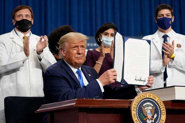 President Trump holds up an executive order after delivering remarks on health care in Charlotte, N.C., on Thursday.