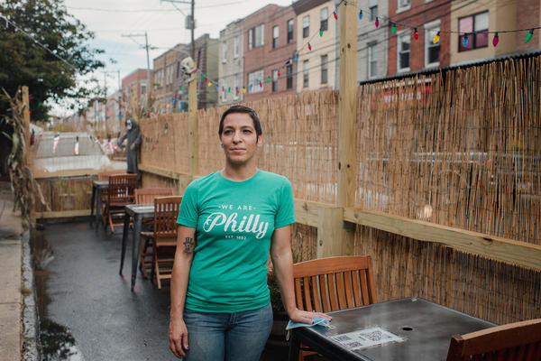 Danielle Renzulli, owner of 12 Steps Down Bar in Philadelphia, poses by the tables she has set up in what used to be parking spots. She was expecting some negative reactions from neighbors, given how valuable parking is in the area, but to her surprise, she received no complaints.