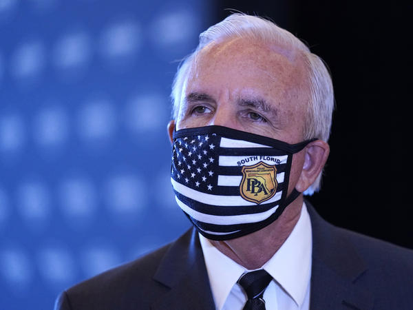 Miami-Dade County Mayor Carlos Gimenez speaks with the news media, last month, at Hard Rock Stadium in Miami Gardens, Fla. Gimenez said Tuesday that he would keep some COVID-19 restrictions in place despite an order by Fla. Gov. Ron DeSantis.