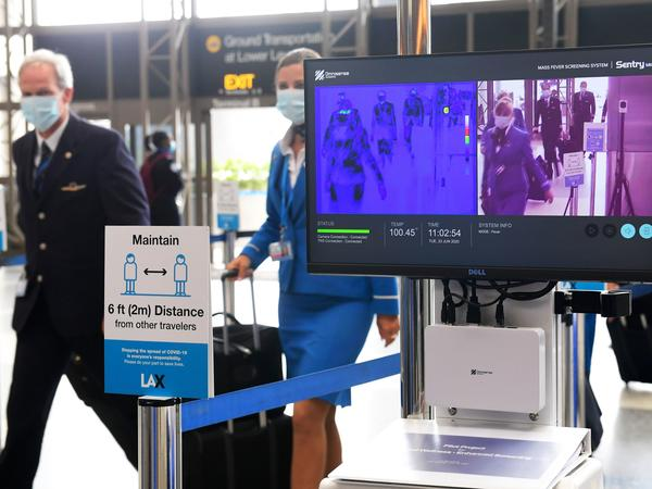 Flight crew members walk past thermal cameras that check passengers' body temperatures at Los Angeles International Airport on June 23. As businesses look to reopen, technology firms are offering an array of monitoring systems to try to control the coronavirus.