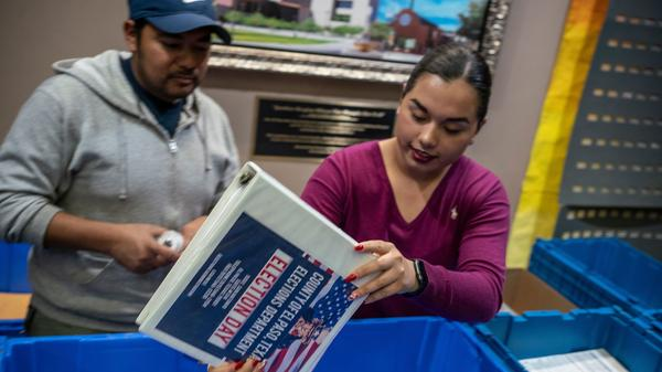 Jonathan Lucero and Valeria Gutierrez prepare to receive ballots at the El Paso County Courthouse during the presidential primary in March.