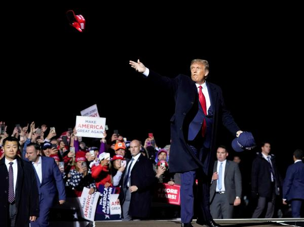 President Donald Trump throws hats to supporters after speaking Wednesday at a campaign rally at Duluth International Airport in Minnesota.