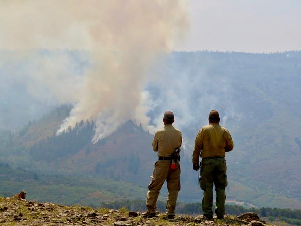 Firefighters watch a controlled burn within the Grizzly Creek Fire in Colorado. The fire has burned more than 30,000 acres near Glenwood Canyon. Now, the charred hillsides pose a flood risk for nearby areas.