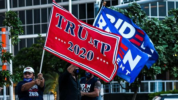 Supporters of President Trump and Democratic presidential nominee Joe Biden wave flags prior to Biden's arrival for a town hall in Miami.