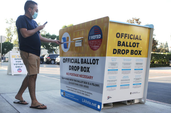 A voter places a ballot in an official mail-in ballot drop box outside the Los Angeles County Registrar's office this week in Norwalk, Calif. The California Republican Party has said it will not comply with a state cease-and-desist order to halt usage of the GOP's unofficial ballot drop boxes.