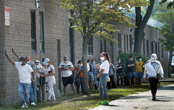 People wait in the shade while in line to get coronavirus tests in Revere, Mass.