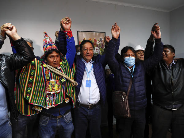 Bolivian presidential candidate Luis Arce (center) and running mate David Choquehuanca (second right) celebrate during a news conference Monday in La Paz, Bolivia.
