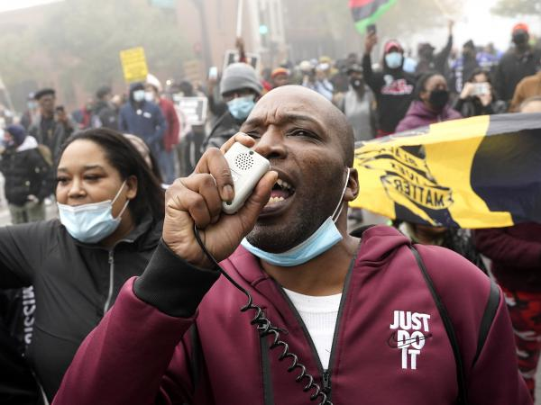 Rayon Edwards rallies protesters during a march Thursday for Marcellis Stinnette, who was killed by police in Waukegan, Ill.