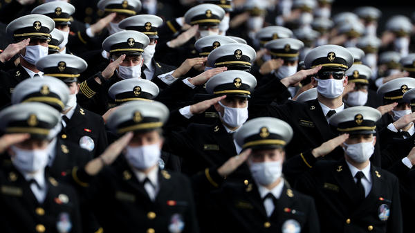 Midshipmen wearing face masks stand and salute before the Navy Midshipmen play against the Houston Cougars on Saturday in Annapolis, Md. Researchers have tried to estimate how many lives would be saved by universal mask-wearing.