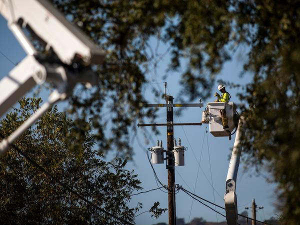 A PG&E contractor works on utility poles along Highway 128 near Geyserville, Calif., on October 31, 2019. The utility is shutting off power for hundreds of thousands in an effort to not spark wildfires.