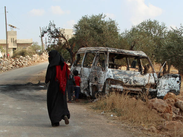 A woman walks past a wrecked van near the northwestern Syrian village of Barisha. Local residents and medical staff told NPR that noncombatant civilians who were in the van were injured and killed last year the night of the U.S. raid on the compound of ISIS leader Abu Bakr al-Baghdadi. The military says the men were combatants but found no weapons.