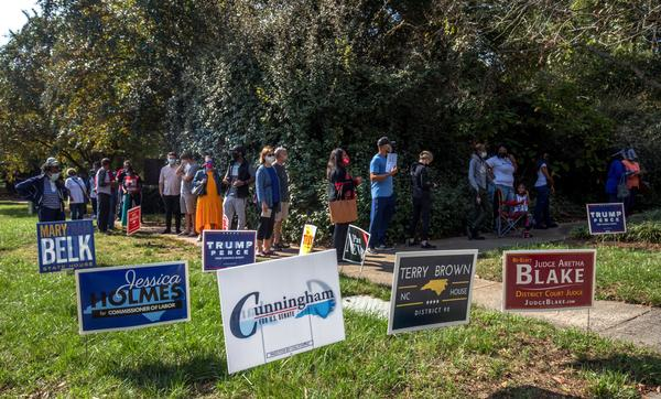 Voters in Charlotte, North Carolina, wait in line to cast their ballots at the West Boulevard branch of the Mecklenburg County library on October 15, 2020, the first day of early voting. (Grant Baldwin/AFP via Getty Images)
