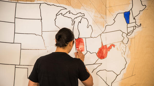 An artist paints a mural indicating which presidential candidate has won certain states on election night in 2016. Once again, NPR will rely on The Associated Press to provide election results and race calls.