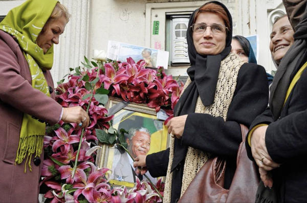 Iranian human rights lawyer Nasrin Sotoudeh with a poster of South Africa's Nelson Mandela, in a scene from the <em>Nasrin </em>documentary.