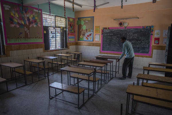 An employee adjusts desks in an empty classroom in New Delhi after schools there were closed in March. A new report finds 1 in 4 countries have either missed their planned school reopening date, or not yet set one.
