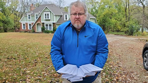 Doug Reed holds the dozens of letters from the Kansas Department of Labor that were mailed to his dad's former house and appear to be a sign of unemployment fraud.