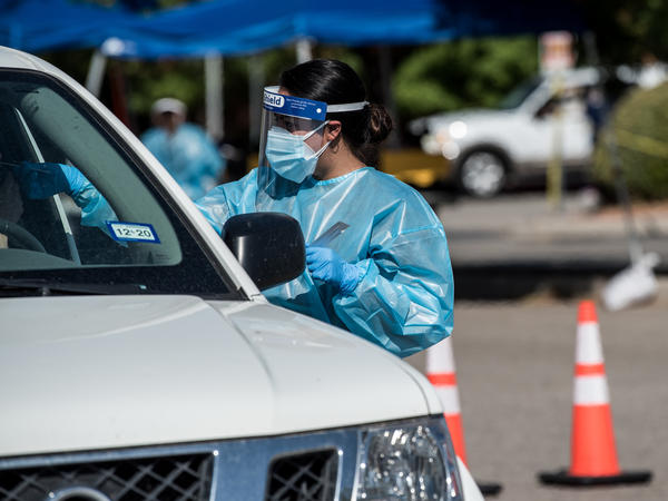 A nurse conducts a coronavirus test at a mega drive-through site in July at El Paso Community College's Valle Verde campus in El Paso, Texas.