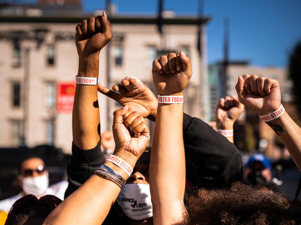"""Black Lives Matter protesters display wristbands reading """"I Voted"""" after leaving a polling place this month in Louisville, Ky. Activists warn Black and Latino voters are being flooded with disinformation intended to suppress turnout in the election's final days."""