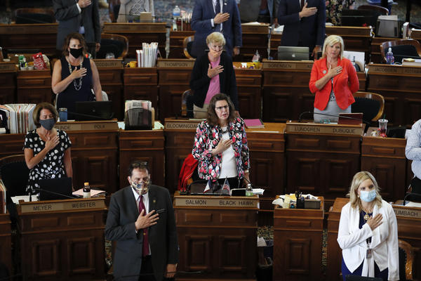 State representatives stand during the Pledge of Allegiance in the Iowa House chambers in Des Moines, Iowa, in June.