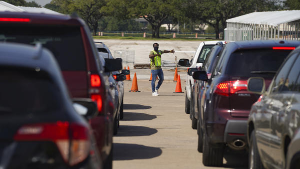 An election worker guides voters in cars at a drive-through voting site in Houston on Oct. 7.