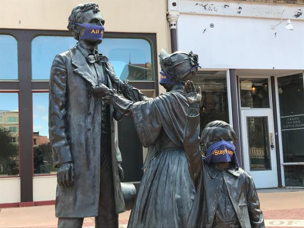 Masks on statues of Abraham and Mary Todd Lincoln in downtown Springfield