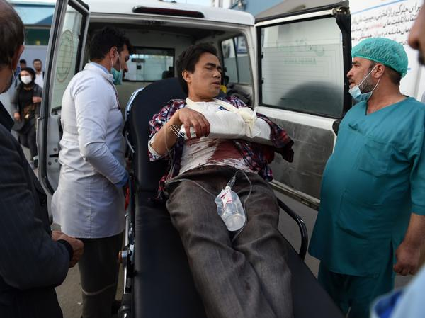 A man, wounded after gunmen stormed Kabul University, arrives in an ambulance at Isteqlal Hospital on Monday. At least 19 people died in the attack on Afghanistan's largest university.
