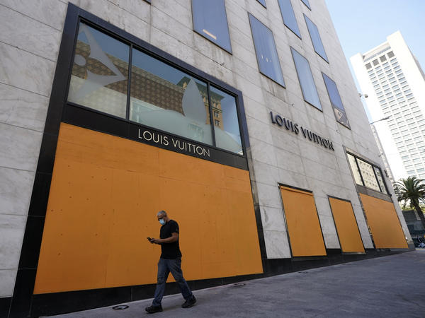 A man walks past a boarded-up window of a Louis Vuitton store in San Francisco on Sunday.