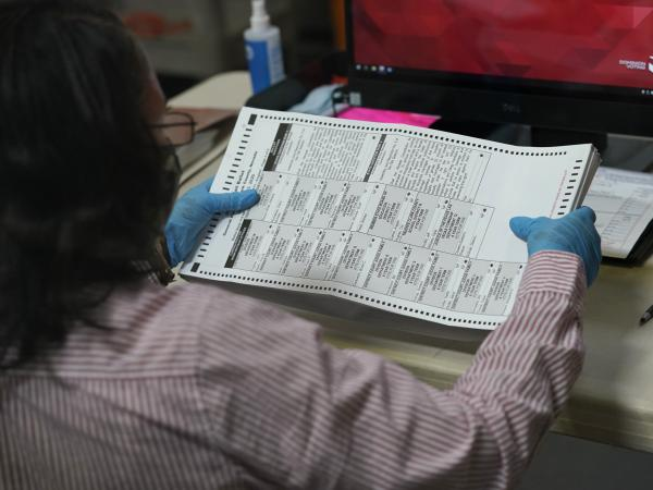 A county worker loads mail-in ballots into a scanner that records the votes at the Clark County Election Department last Thursday in Las Vegas.
