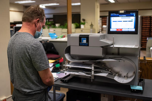 Tabulator operator Jeff Sillick cycles roughly 35 ballots through an automatic counting machine in the Lewis and Clark County elections office on Nov. 2, 2020.