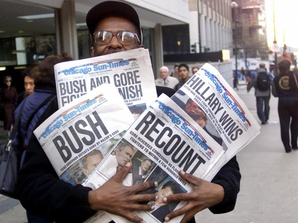 A man holds four copies of the Chicago Sun-Times, each with a different headline, on Nov. 8, 2000.