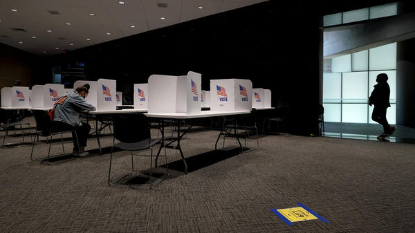 A poll worker (right) waits while a woman votes Tuesday at the National World War I Museum & Memorial in Kansas City, Mo.
