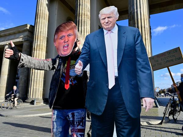 A supporter of President Trump poses with a cardboard-cutout likeness Wednesday in front of the Brandenburg Gate in Berlin.