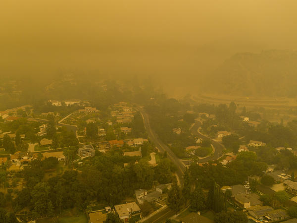 Climate change has been a key factor in increasing the risk and extent of wildfires and other catastrophic weather events. Here, an aerial view shows neighborhoods in Monrovia, Calif., shrouded in smoke from the Bobcat Fire in September.