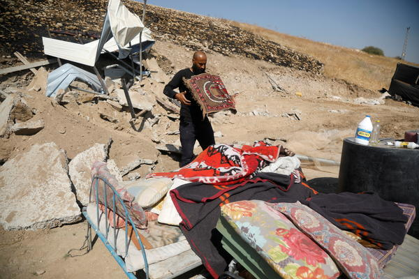 A Palestinian man collects his belongings after his structure was demolished by Israeli forces in the Jordan Valley in the Israeli-occupied West Bank on Oct. 19. Palestinian groups say another hamlet was destroyed in the same area on Tuesday.