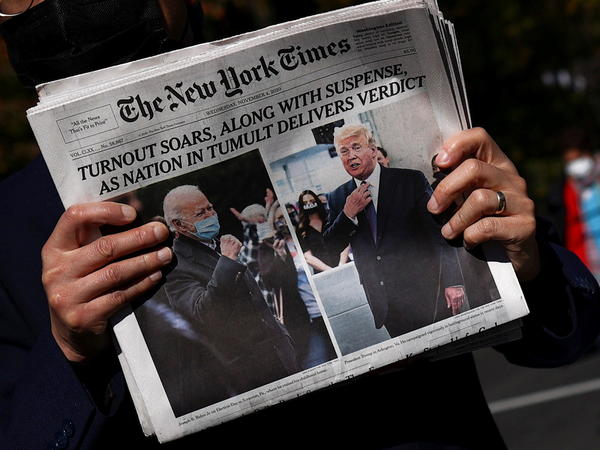 A man holds a fresh copy of <em>The New York Times</em> on Wednesday morning on Black Lives Matter Plaza near the White House.