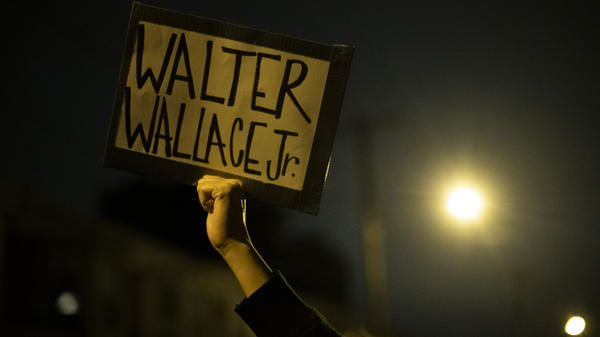 A demonstrator holds a placard with Walter Wallace Jr.'s name on it during a protest near the location where he was killed by two police officers in Philadelphia.