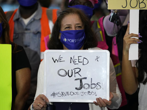 "A woman holds a sign saying ""We Need Our Jobs"" during a protest by workers in the cruise ship industry in Miami last month. Employers added fewer jobs as pandemic cases start to surge again across the country."