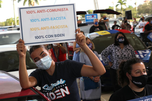 Wearing a face masks to reduce the risk posed by the coronavirus, Sophia Hildalgo (L) and Amore Rodriguez of Miami stay with their car decorated in Cubans for Biden paint.
